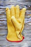 De gele handschoenen van de leerveiligheid op houten raad Royalty-vrije Stock Foto