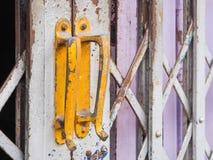De gele handvatten van de staaldeur van de oude schuifdeur Stock Foto's