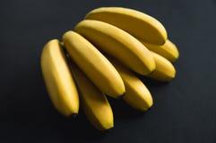 De gele heldere rijpe bananen liggen op een zwarte achtergrond Heerlijke banaantak fruit op een zwarte achtergrond stock afbeeldingen