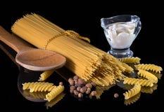 De gele Italiaanse die deegwaren, spaghetti, zwarte peper tegen de zwarte wordt geïsoleerd isoleerden achtergrond Een mooi stille royalty-vrije stock afbeelding