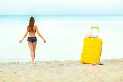 De gele koffer op het strand en een meisje loopt in het overzees in Th Stock Afbeeldingen