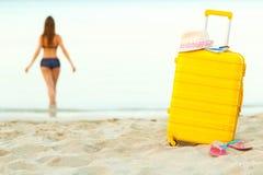 De gele koffer op het strand en een meisje loopt in het overzees in Th Royalty-vrije Stock Fotografie
