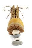 De gele laarzen die zich op een piramide van stenen bevinden Stock Afbeelding