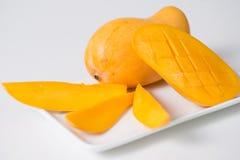 De gele mango en de plakken van mango zijn op de witte plaat Ge?soleerde achtergrond stock foto