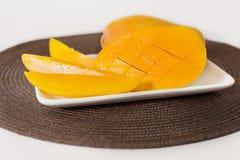 De gele mango en de plakken van mango zijn op de witte plaat Het bruine tafelkleed is onder de plaat stock fotografie