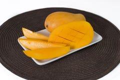De gele mango en de plakken van mango zijn op de witte plaat Het bruine tafelkleed is onder de plaat stock foto