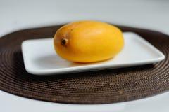 De gele mango is op de witte plaat Het bruine tafelkleed is onder de plaat stock foto's