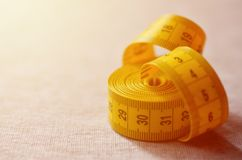 De gele metende band met numerieke indicatoren in de vorm van centimeters of duim ligt op een grijze gebreide stof Conceptenindus Stock Afbeelding