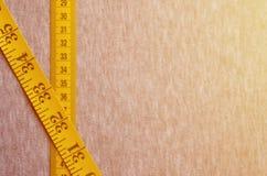 De gele metende band met numerieke indicatoren in de vorm van centimeters of duim ligt op een grijze gebreide stof Conceptenindus Stock Foto's