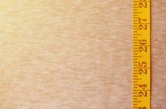 De gele metende band met numerieke indicatoren in de vorm van centimeters of duim ligt op een grijze gebreide stof Conceptenindus Royalty-vrije Stock Foto