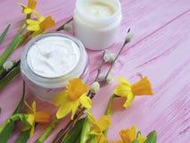 De gele narcissen romen kosmetisch het product gezichtsmasker van de luchtbeschermingscontainer op roze houten natuurlijk af stock foto's