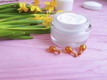 De gele narcissen romen de kosmetische capsules van het het product gezichtsmasker van de luchtbeschermingscontainer op roze hout royalty-vrije stock fotografie