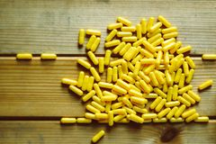 De gele pillen en tablettenachtergrond van het het conceptenidee van de capsulesgezondheid stock foto