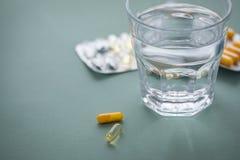 De gele pillen, de tabletten en de capsules in geneeskunde verschroeien met glas water stock fotografie