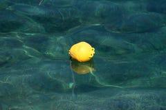 De gele plastic boei die op kalme duidelijke overzees met zichtbare rotsen en gebonden kabel drijven verbond met bodem royalty-vrije stock afbeeldingen