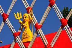 De gele pop van de kleurenklei op één of andere Parallellogrammenstructuur van houten stokken bond met rode kabels en een rode ac royalty-vrije stock afbeelding