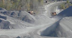 De gele ritten van de stortplaatsvrachtwagen in granietsteengroeve, het werk proces in granietsteengroeve stock footage