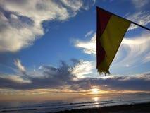 De gele rode vlag op het strand stock foto