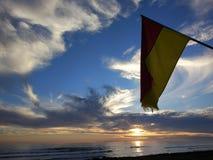 De gele rode vlag op het strand royalty-vrije stock fotografie