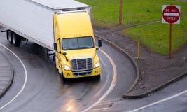De gele semi vrachtwagen en adelborstaanhangwagen zet weguitgang aan royalty-vrije stock afbeeldingen