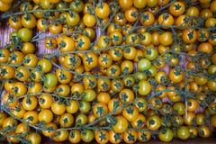 De gele tak van kersentomaten op een houten lijstachtergrond, close-up royalty-vrije stock foto's