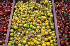 De gele tak van kersentomaten op een houten lijstachtergrond, close-up stock foto