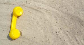 De gele telefoon van een oude uitstekende telefoon ligt op het zand met een exemplaarruimte voor uw tekst met contacten stock foto