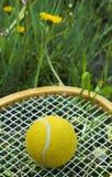 De gele tennisbal is op de racket in het gras Royalty-vrije Stock Afbeeldingen