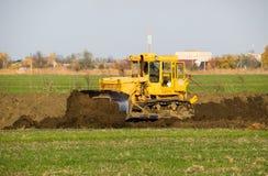 De gele tractor met in bijlage grederom maakt grond het nivelleren stock foto's