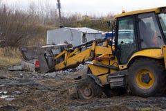 De gele tractor met de emmer wordt genivelleerd de grond stock afbeeldingen