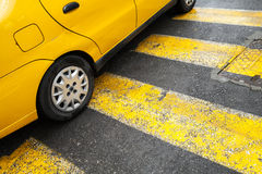 De gele tribunes van de taxiauto bij de voetgangersoversteekplaats Royalty-vrije Stock Fotografie