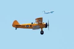 De gele tweedekker presteert bij airshow met commerciële vlucht in wedijvert royalty-vrije stock foto's