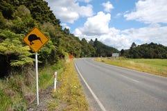 De gele verkeersteken van de kiwivogel bij kant van de weg stock foto's