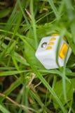 De gele witte kubus antistress in gras, wordt antistresskubus verloren Stock Foto
