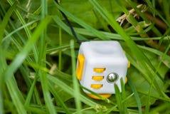 De gele witte kubus antistress in gras, wordt antistresskubus verloren Stock Fotografie