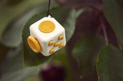 De gele witte kubus antistress op hout, friemelt Kubus Eenvoudige Spanning Stock Fotografie