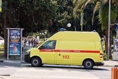 De gele ziekenwagenbestelwagen is bij de kruising van straten van Re Stock Foto