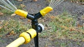 De gele zwarte het water geven gazonsprenkelinstallatie bespuit water stock videobeelden