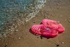 De GELEI SANDALS van roze Vrouwen op een overzeese kust SCHOENEN VAN HET DE ZOMERstrand VAN DAMES DE VLAKKE GELEI stock afbeelding
