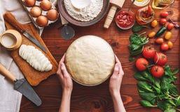 De geleidelijke werkgever maakt een pizza Margarita Deeg en pizza ingre Royalty-vrije Stock Foto