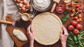 De geleidelijke werkgever maakt een pizza Margarita Deeg en pizza ingre Royalty-vrije Stock Fotografie