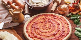 De geleidelijke werkgever maakt een pizza Margarita Deeg en pizza ingre Royalty-vrije Stock Afbeeldingen