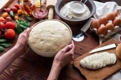 De geleidelijke werkgever maakt een pizza Margarita Deeg en pizzaingrediënten Stock Foto's
