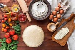 De geleidelijke werkgever maakt een pizza Margarita Deeg en pizzaingrediënten Royalty-vrije Stock Afbeeldingen
