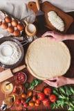 De geleidelijke werkgever maakt een pizza Margarita Deeg en pizzaingrediënten Royalty-vrije Stock Foto