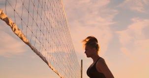 De de gelijkemeisjes van het strandvolleyball raken de bal in langzame motie bij zonsondergang op het zand stock video