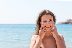 De gelooide vrouw beschermt haar gezicht met zonroom tegen zonnebrand bij het strand stock fotografie