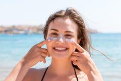 De gelooide vrouw beschermt haar gezicht met zonroom tegen zonnebrand bij het strand stock afbeelding