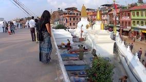 De gelovigen rekken zich dichtbij een grote stupa uit stock video
