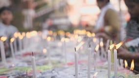 De gelovigen zetten witte kaarsen naast een Katholieke tempel in India stock footage